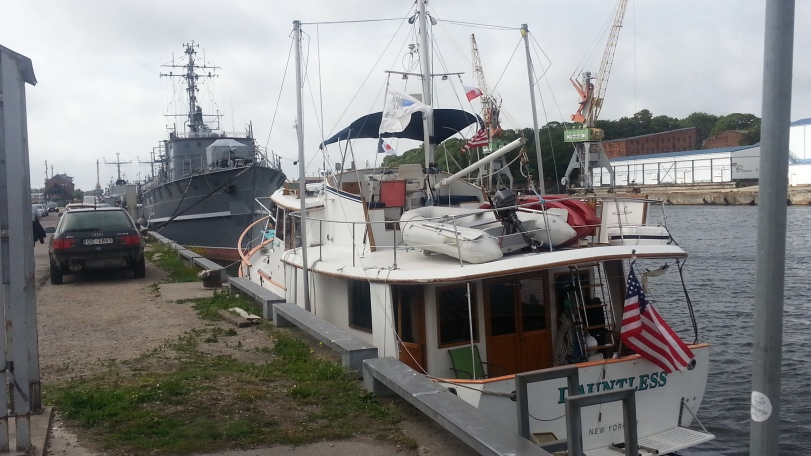 Dauntless in Liepaja docked in front of a warship